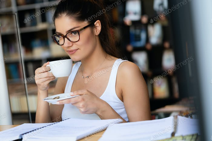 Portrait of young beautiful smiling woman working or studying