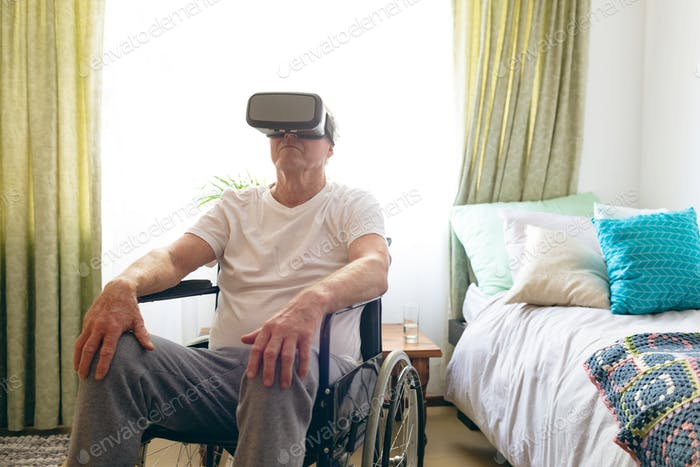 Senior Caucasian male patient using virtual reality headset in wheelchair at retirement home