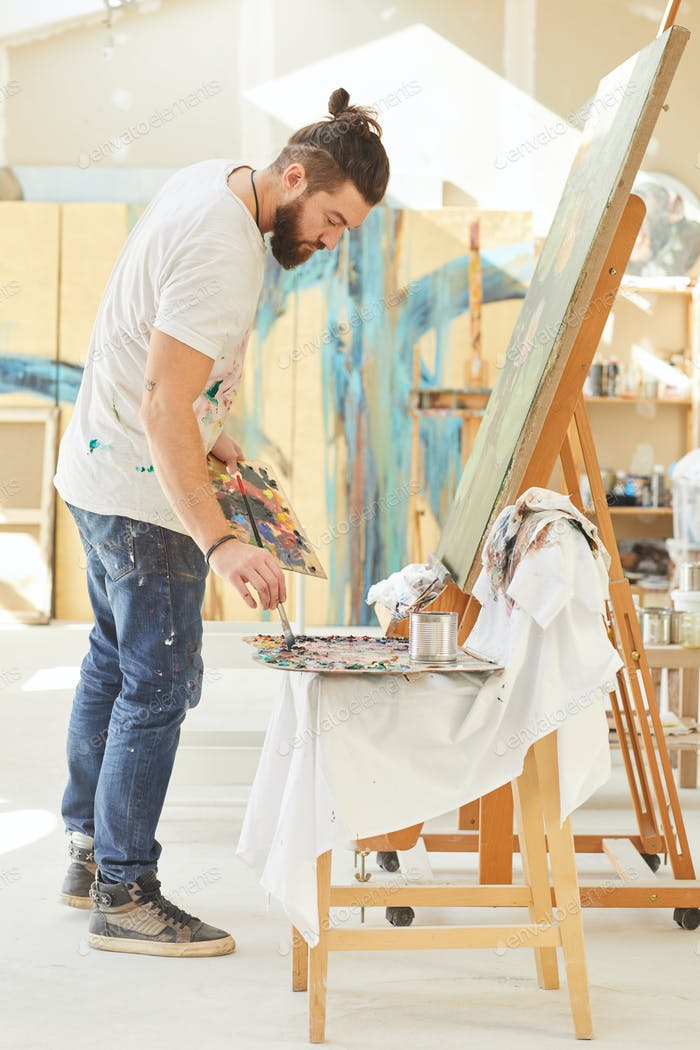 Male Artist Painting Picture in Workshop