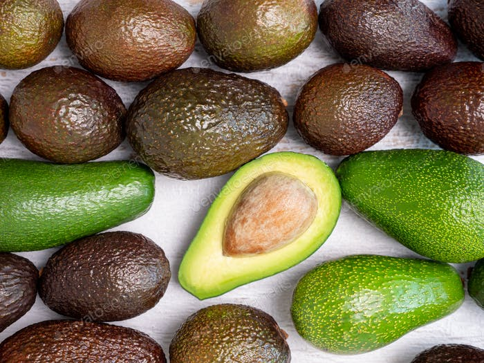 Mix of ripped and green avocados on white wooden board