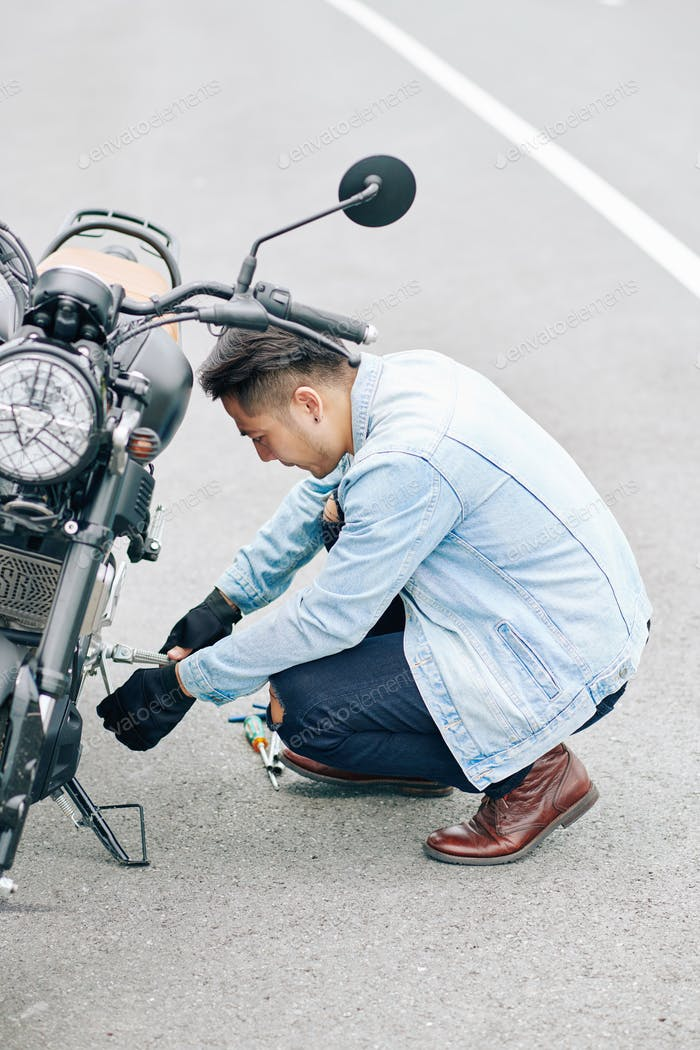 Man inspecting motorcycle