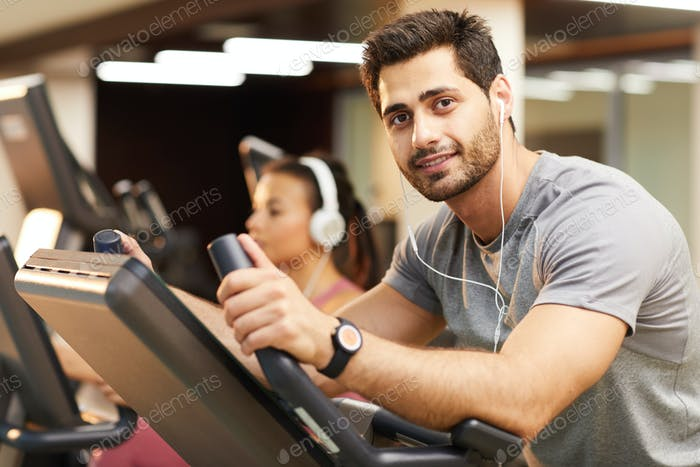 Handsome Man Using Exercise Bike in Gym