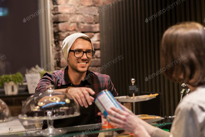 man or barman serving customer at vegan cafe