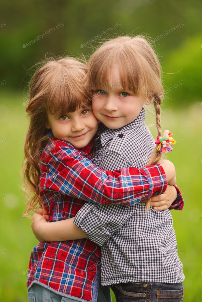 two girls hugging each other on green