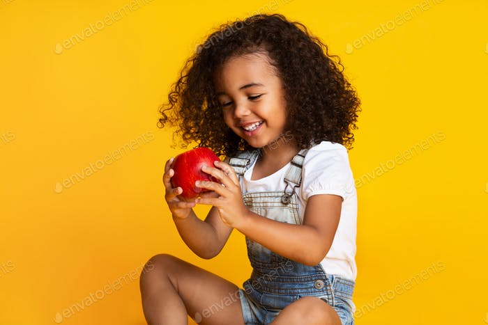 Pretty girl holding red apple over yellow studio background