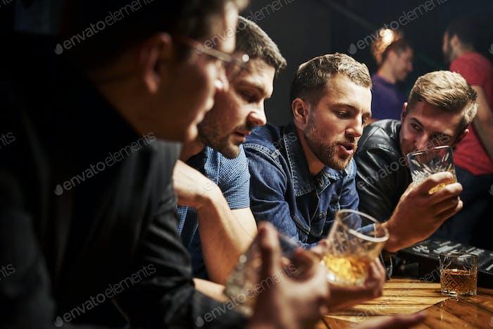 Seitenansicht. Freunde ruhen in der Kneipe mit Alkohol in den Händen. Konversation haben