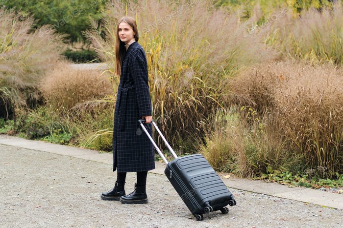 Beautiful girl in coat with suitcase dreamily looking in camera outdoor