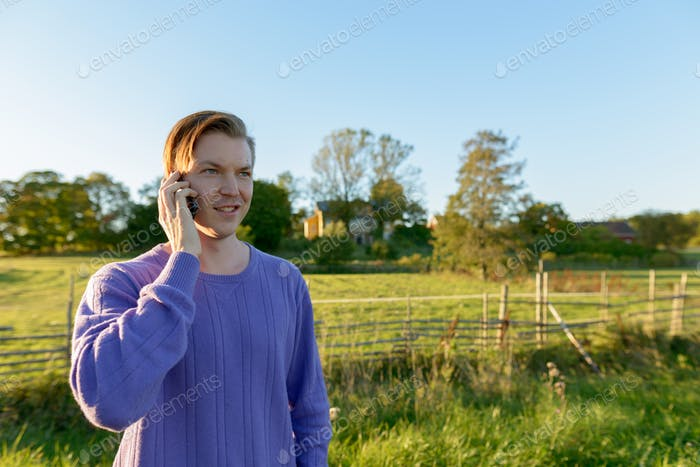 Happy young man talking on mobile phone in peaceful grassy plain with nature