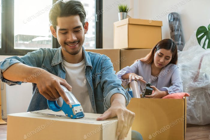 Asian young couple packing big cardboard box for moving in new house
