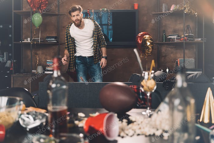 Upset bearded young man with hangover standing in messy room after party