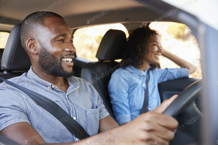Young black couple in car on a road trip look ahead smiling