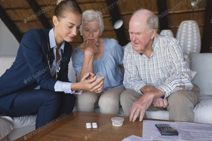 Female doctor and senior couple discussing over medicine at home