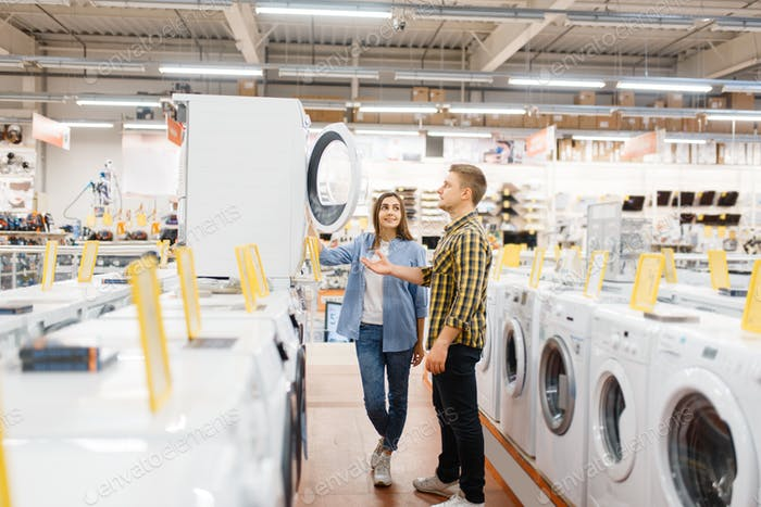 Couple choosing washing machine, electronics store