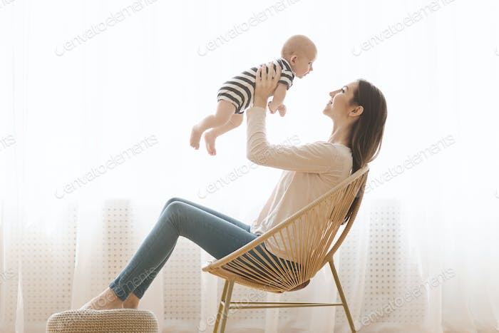 Mother sitting in wicker chair and playing with newborn child