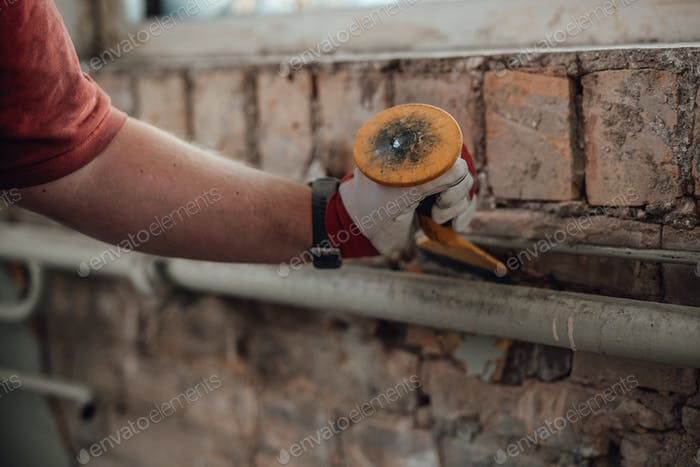 Builder's strong hands working with hammer and chisel at the construction site