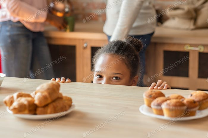 Playful little girl looking secretly at sweets at kitchen
