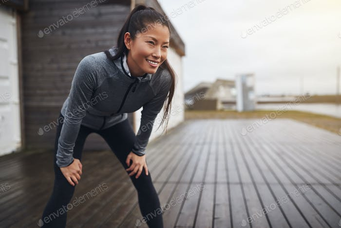 Lächelnd asiatische Frau fangen Ihr atmen während aus joggen