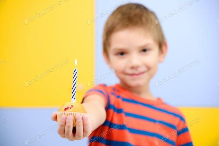 Junge mit Geburtstags-Cupcake