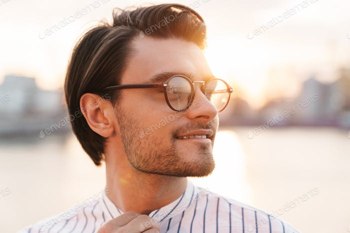 Photo of successful happy man smiling and looking aside while walking on promenade