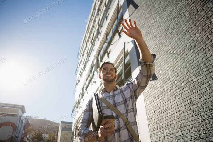 Man holding disposable cup gesturing while walking by building in city