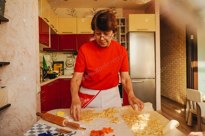 Senior woman cooking cookies in red clothes.