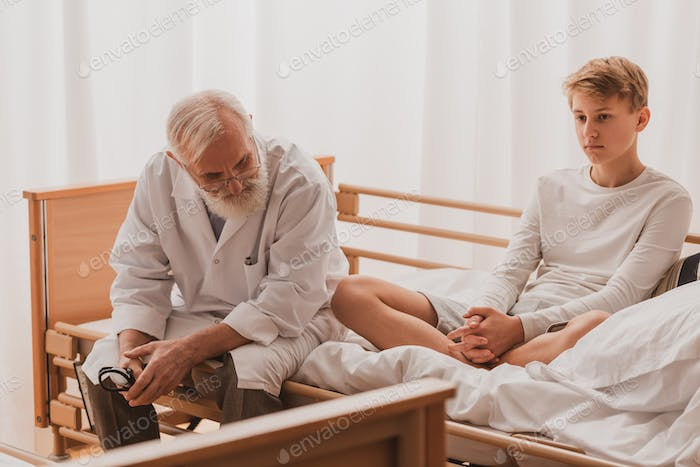 Teenage young patient is sitting cross-legged on a hospital bed during hospitalization