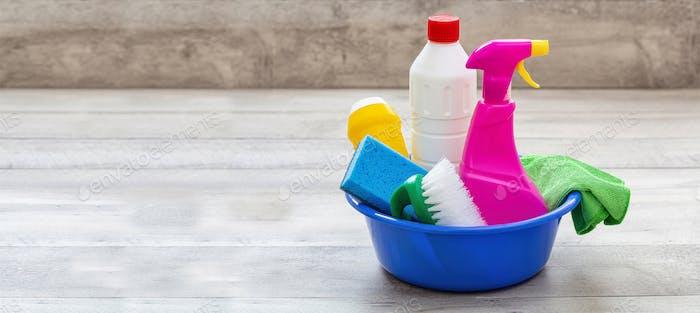 Reinigungsbedarf in einer blauen Schüssel, Holzboden Hintergrund.