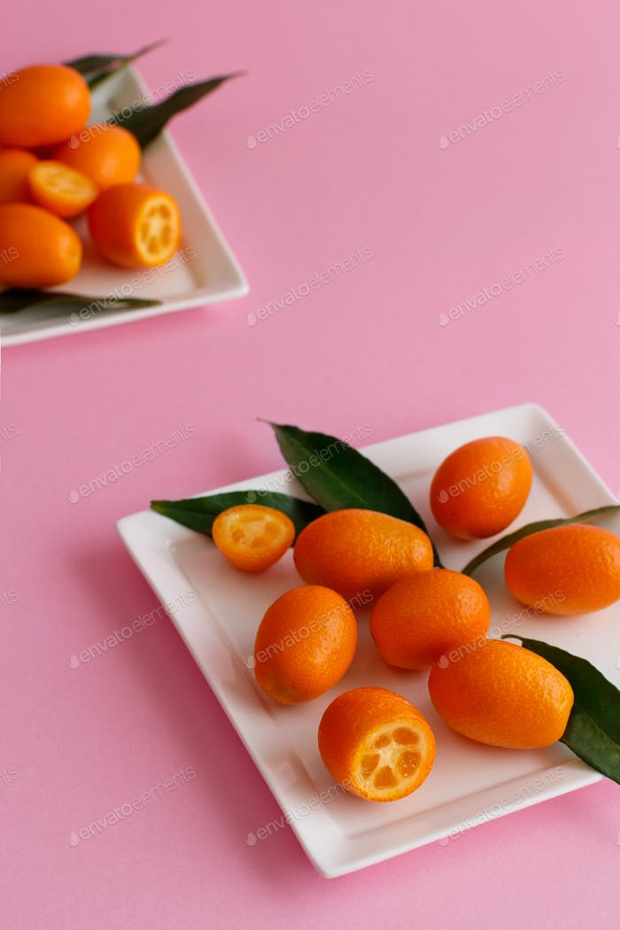 Kumquat fruits on a pink background