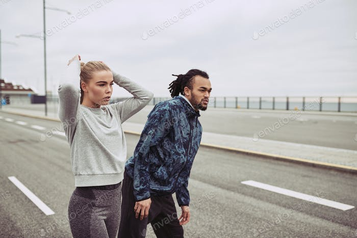 Young couple in sportswear getting focused for a run together