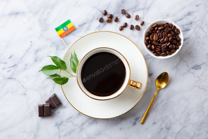 Cup of Coffee with Ethiopia flag on marble table. Top view.