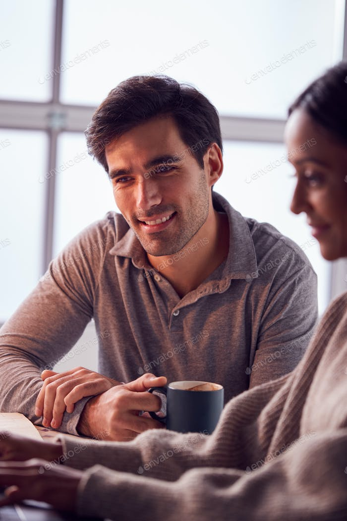 Businesswoman Working On Laptop At Desk Collaborating With Male Colleague Drinking Coffee