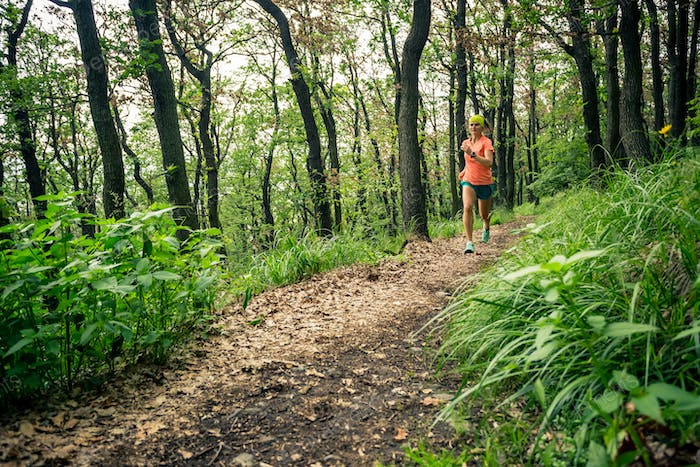Trail running woman in green forest. Endurance sport.