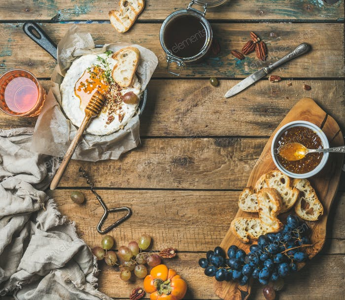 Cheese, fruit, nut and wine set over rustic wooden background