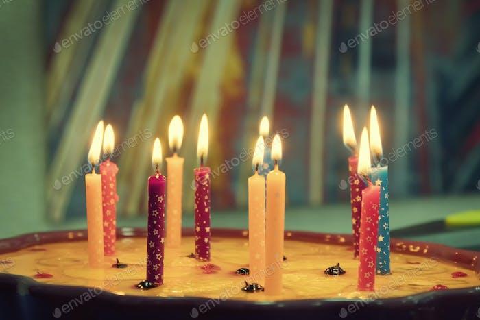 Birthday cake with burning candles. Toning.