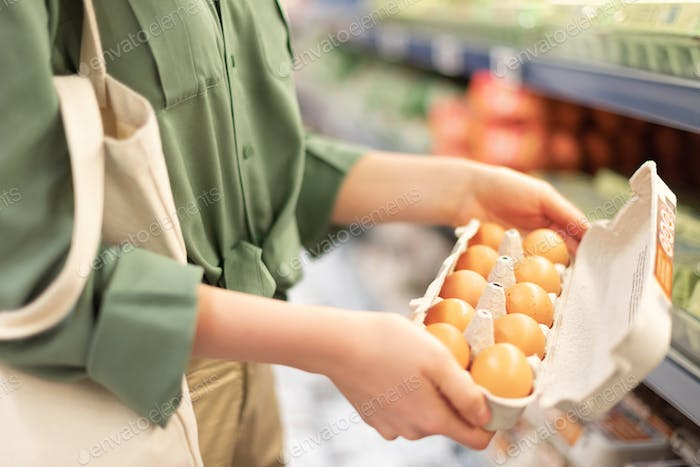 Girl at supermarket holding cotton shopper bag and buying eggs in craft package without plastic bags