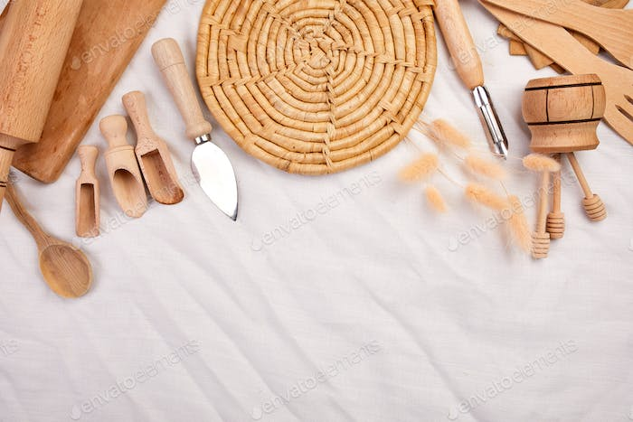 Flat lay with wooden kitchen utensils, cooking tools on textile background