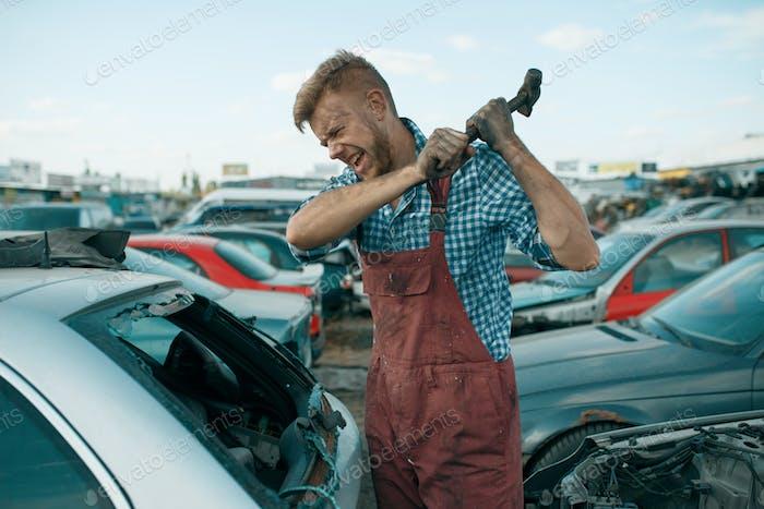 Repairman hits the glass with hammer, car junkyard