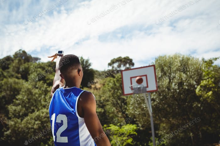 Rear view of male teenager practicing basketball