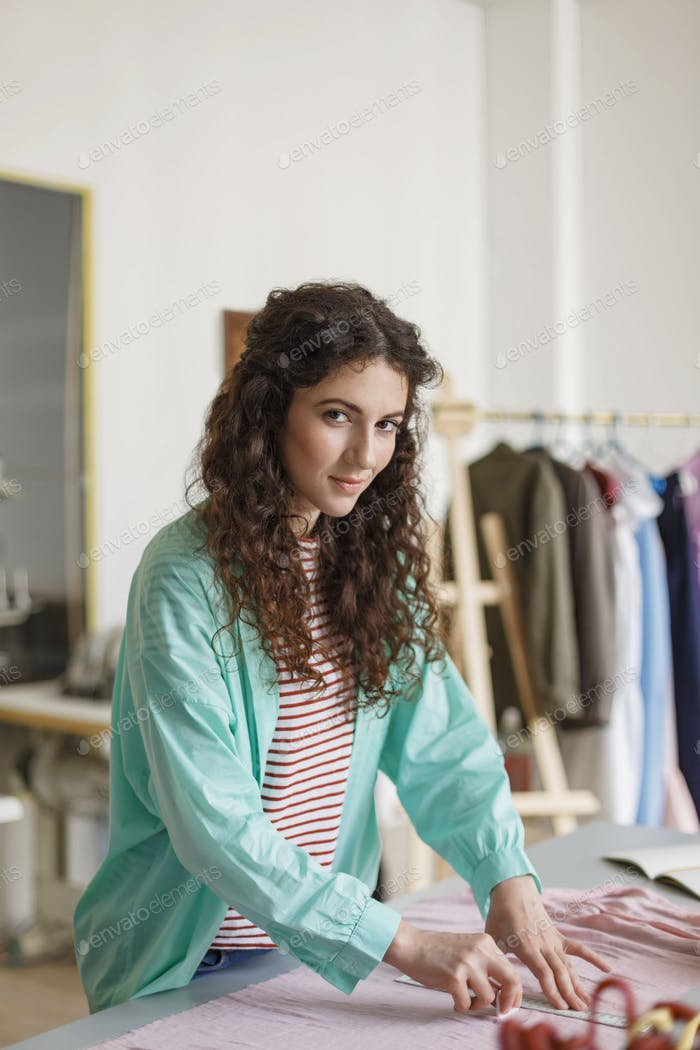 Pretty tailor in shirt and striped T-shirt dreamily looking in c