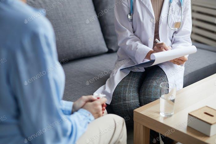 Mujer Doctora Escribiendo en Portapapeles en Consulta