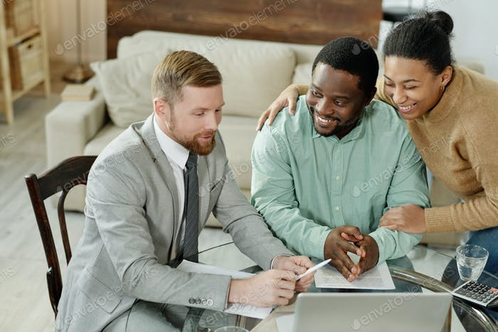 Cheerful ethnic couple talking to financial adviser
