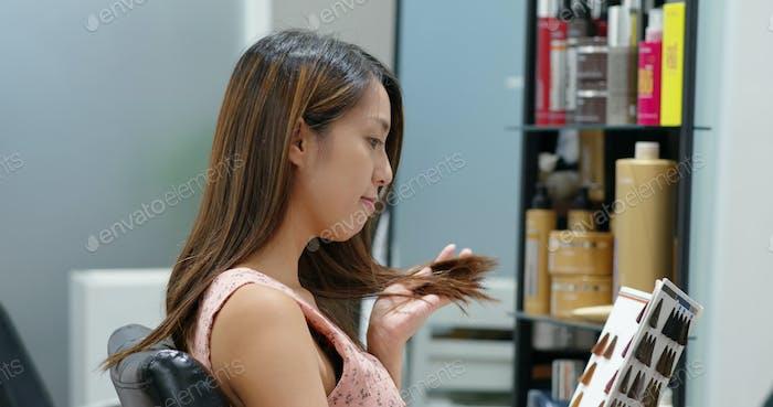 Женщина смотрит на цветную книгу цвета краски для волос в салоне красоты