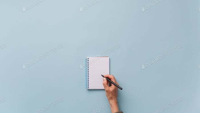 Top view of female hand writing in blank notepad