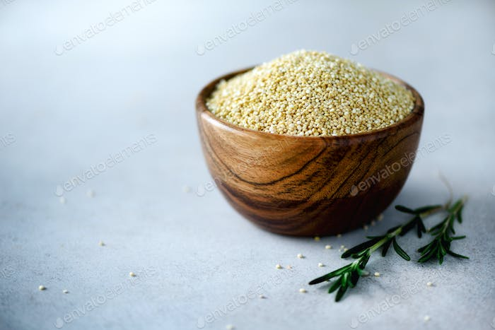 White raw organic quinoa in wooden bowl and rosemary on grey background. Healthy food ingredients