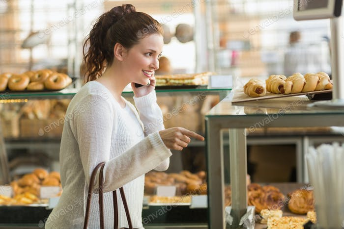 Pretty brunette picking out a pastry at the bakery