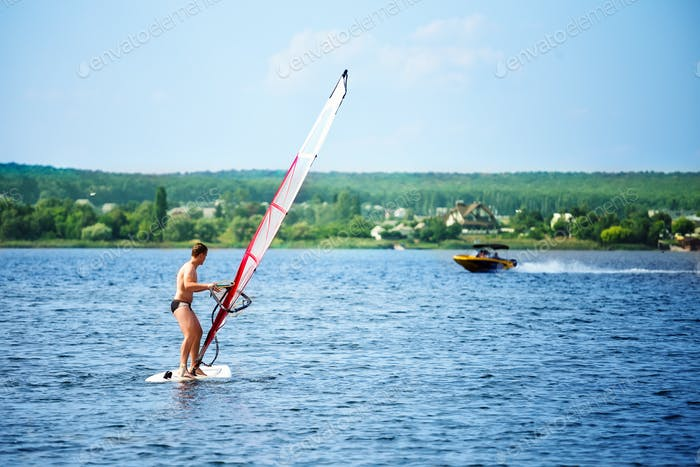 Windsurfer on board with a white sail floating away