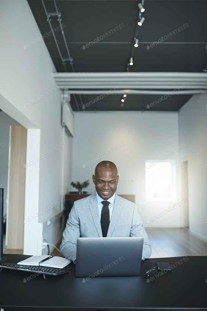 Smiling African American businessman working at his desk