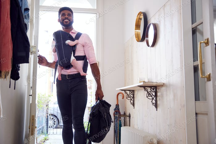 Man Carrying Baby Daughter In Sling Opens Front Door Of House
