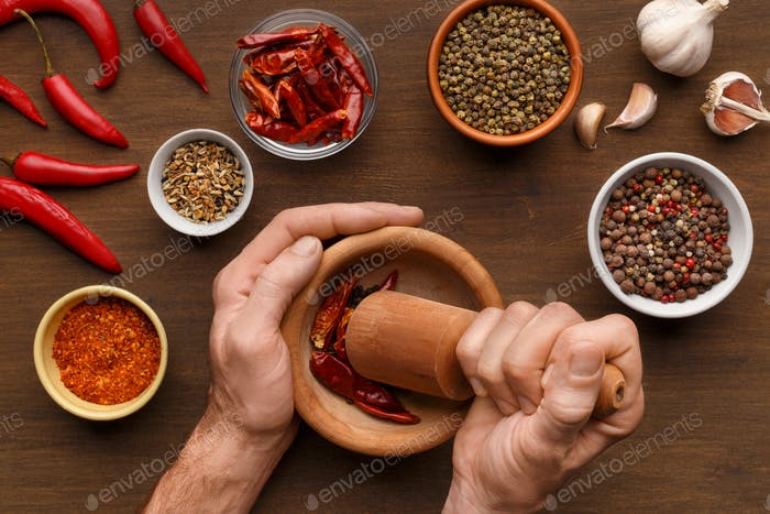 Male hands grinding spices, top view