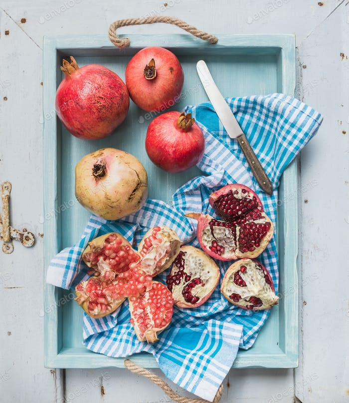 Red and white pomegranates with knife on kitchen towel in blue tray